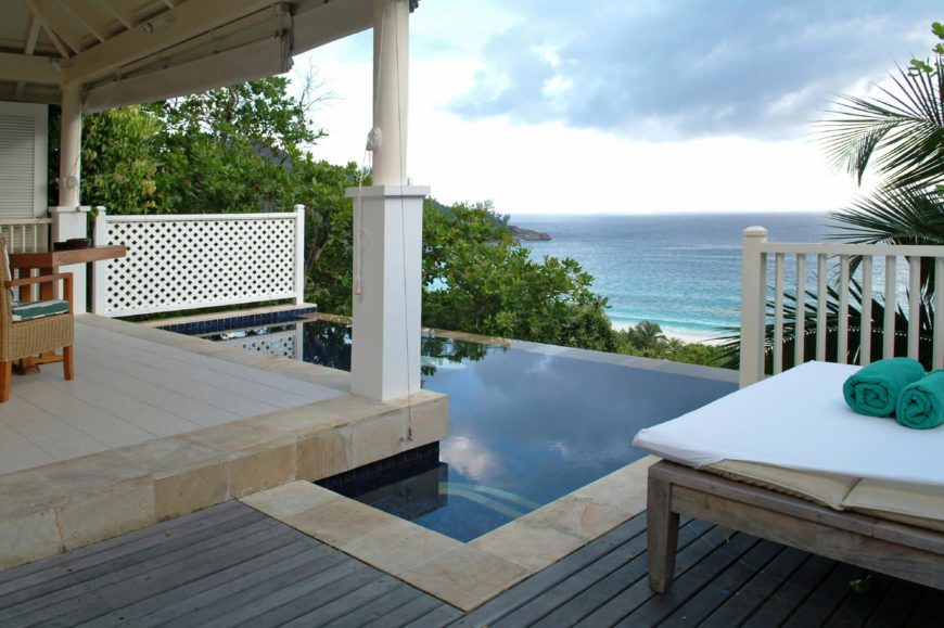 A Small L Shaped Infinity Pool Looking Off The Deck Of A Coastal Beach Home