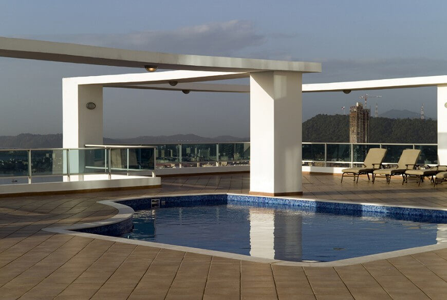 This modern take on the rooftop patio is well lit and has a lovely, private pool. Tinted glass balustrades surround the patio.
