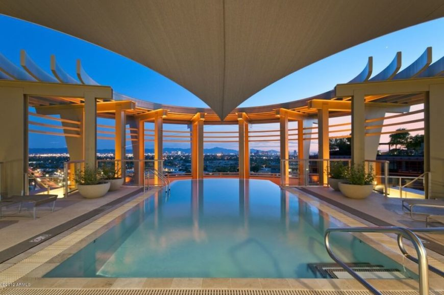 This covered pool is flanked by an enormous half-moon shaped pergola that frames the city skyline beyond the edge of the infinity pool.