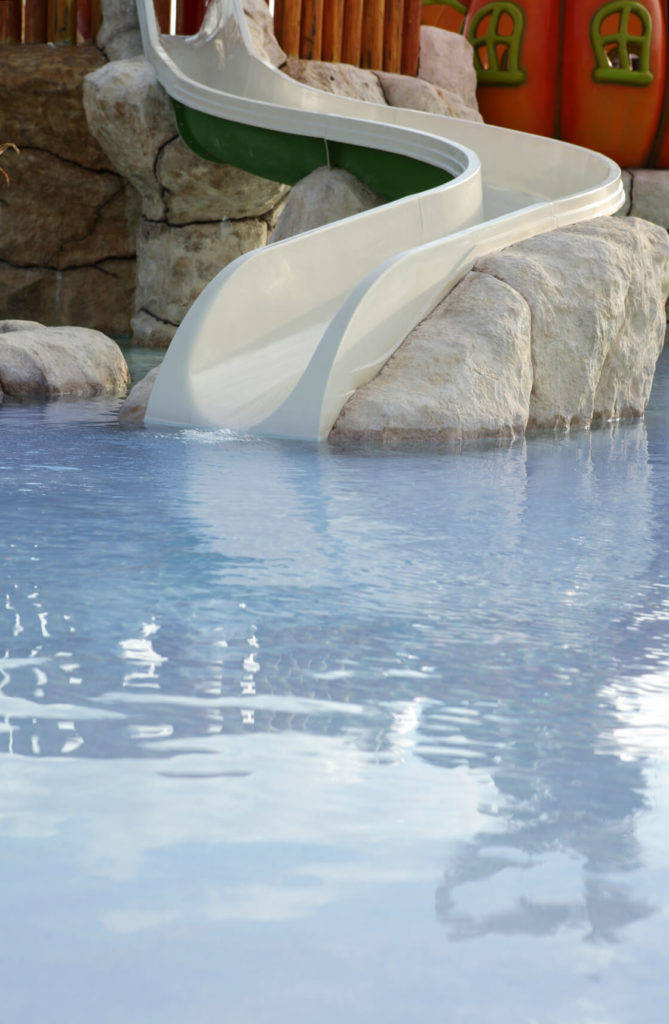 This short, white slide is perched on artificial stones and leads directly into the deep end of a light blue pool.
