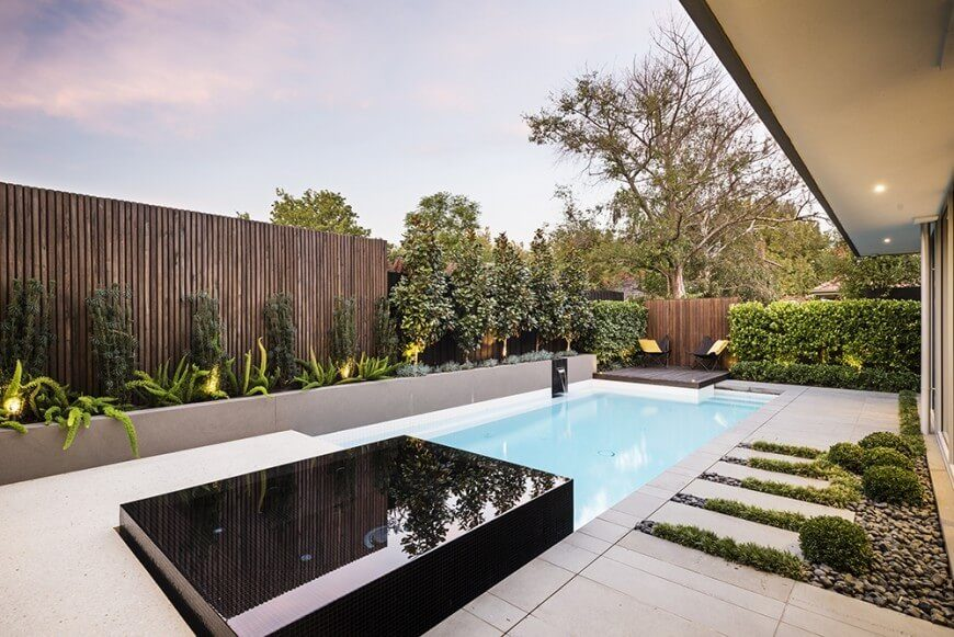 a tall wooden slat fence provides privacy and solitude to this pool