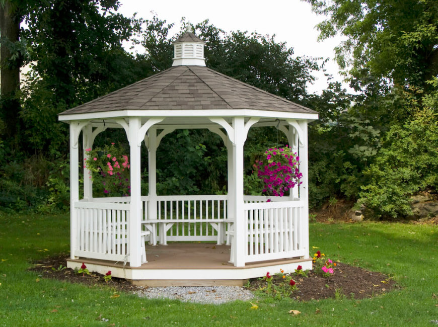 This white hexagonal gazebo features a small planting bed around it and brightly colored hanging baskets of flowers are displayed near the front. Built in benches provide seating.