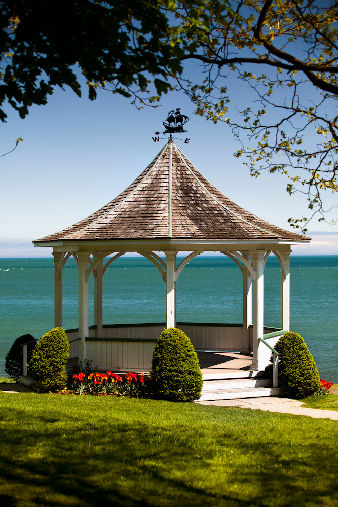 A seaside gazebo flanked by evergreen topiaries and bold red flowers. The view from this structure is gorgeous. Truly a center of outdoor entertaining.