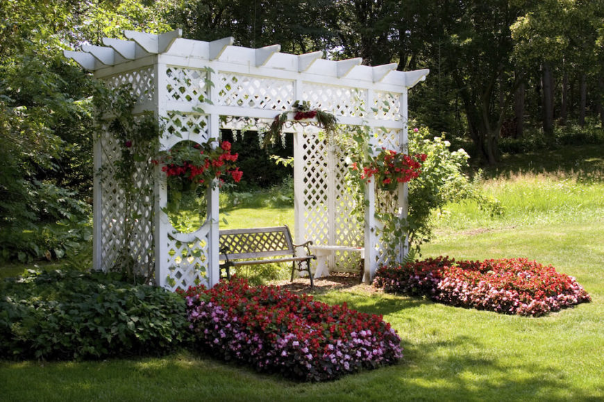 This white pergola is nestled above a small garden patio and bedecked with hanging baskets, climbing vines, and thick beds of flowers. The structure of the pergola is made up of trellises.