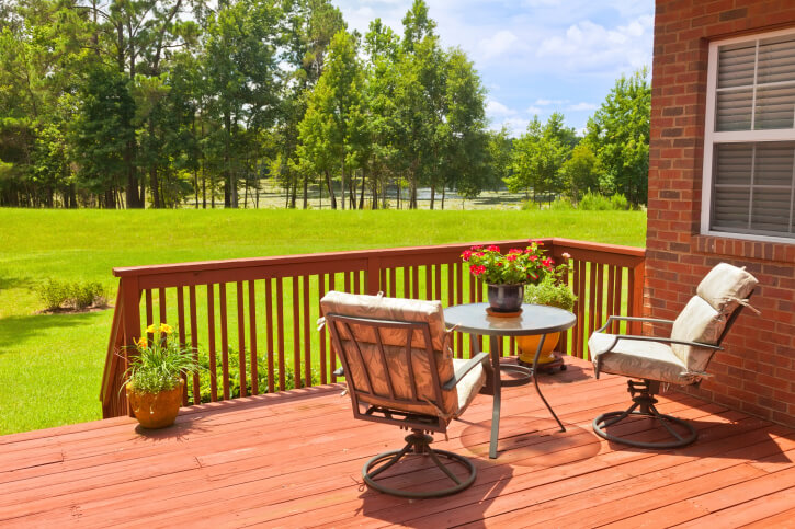 A smaller deck with stairs leading down to the lower section of the yard. A small seating area is positioned perfectly to enjoy the view of the expansive yard that ends in a thin forest.