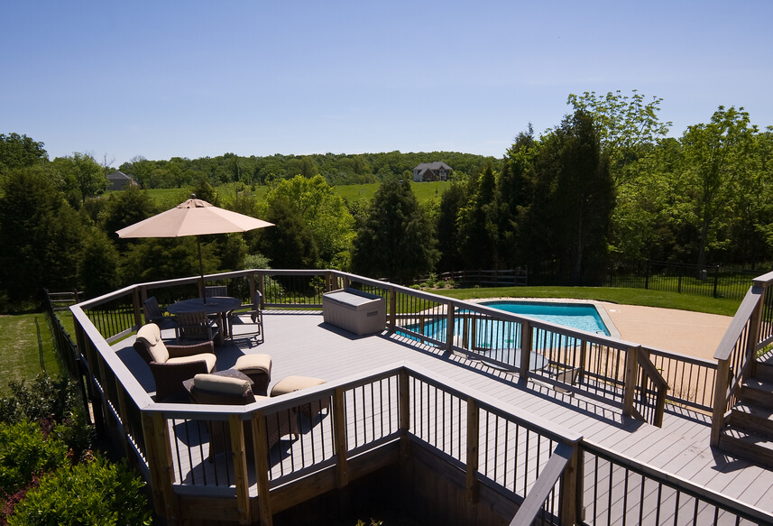 A raised deck overlooking a swimming pool. This deck is surrounded on all sides by a railing and has several different tiers.