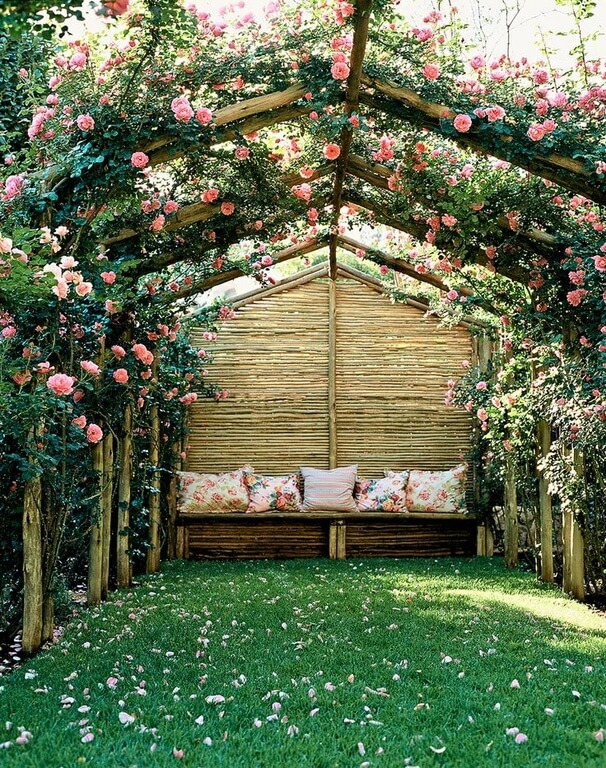 This tall trellis structure creates a tunnel of light pink roses that form a blanket above the small seating area to the rear of the tunnel.