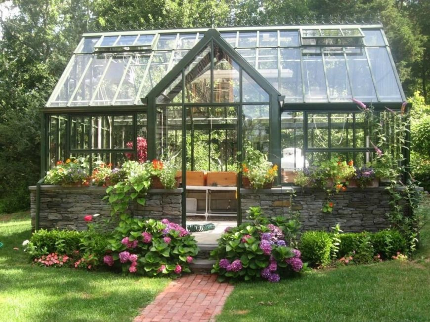Another lovely greenhouse with green structural beams, but the bottom section is built in stacked stone, giving it an all together different appearance.