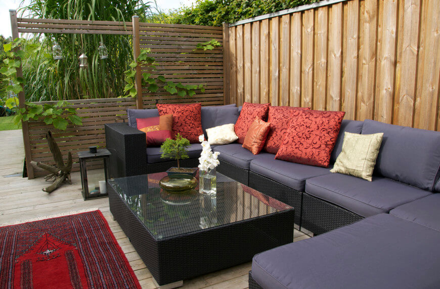 A private seating area is enhanced by adding a wooden screen to one side. Trailing vines draw the seating area back into the garden.