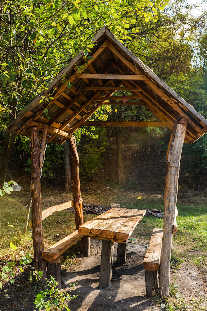 A tiny rustic pavilion with a built-in picnic table. This small area is the perfect spot to stop for a picnic lunch while on a hike.
