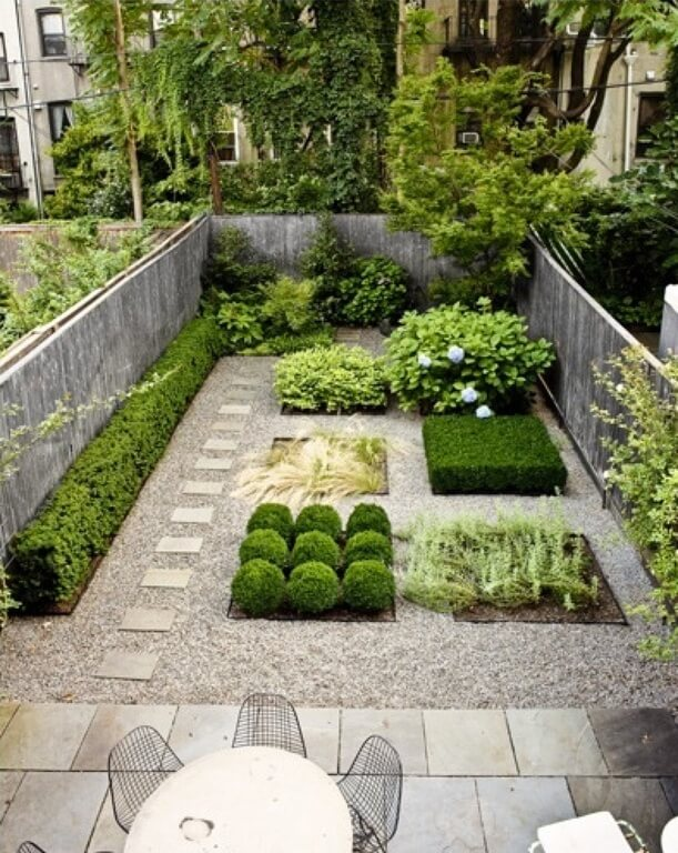 Hedges, topiaries, and other small shrubs are added in small, square sections of this zen garden
