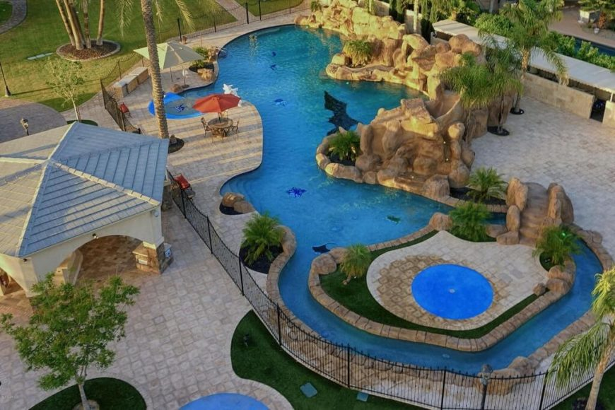 An aerial view allows us to really see this private water park. It has a small lazy river, plenty of coves to play in, and a waterfall along the rocky edge with a slide hidden in those same rocks.