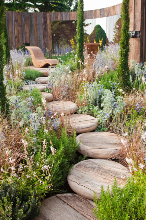 These smooth, rustic stepping stones carve a pathway through dense ground cover landscaping to a patio.