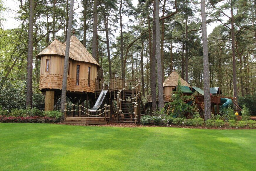 This incredible treehouse is two separate treehouses connected to a massive playset.
