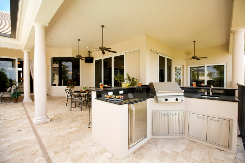 This outdoor kitchen is positioned at the edge of the covered patio and looks back into the dining room, so that the chef may interact with his or her guests.