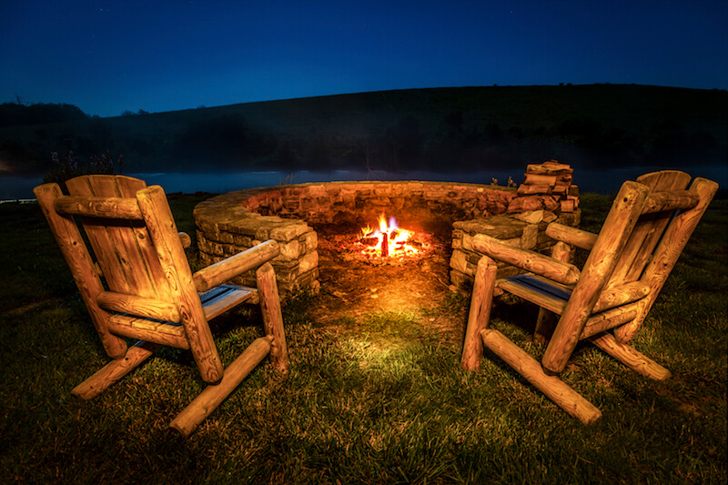 This fire pit is unusual in that it is partially open on one side, which isn't recommended. Two sturdy rustic chairs are positioned on this side, overlooking the view of the lake.