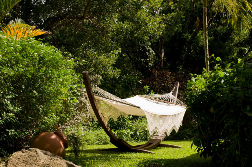 This lovely crocheted hammock is strung between the two ends of a half-circle wooden stand. The hammock sits in a secluded part of the yard amongst the trees.
