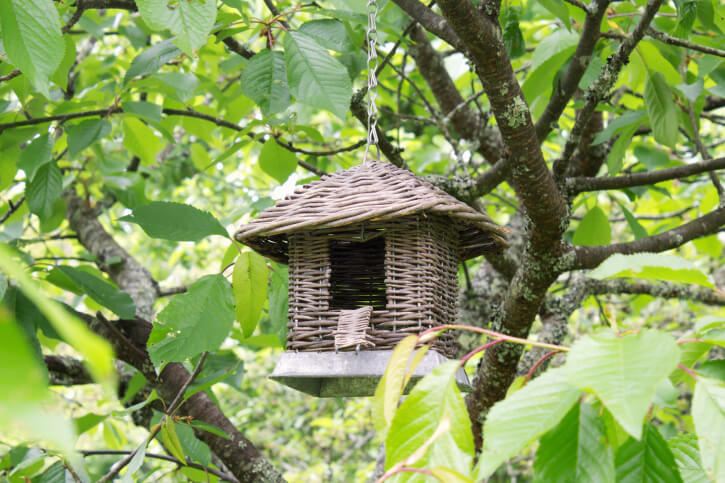 A hanging wicker birdhouse with a door large enough for larger species of birds to fit through.