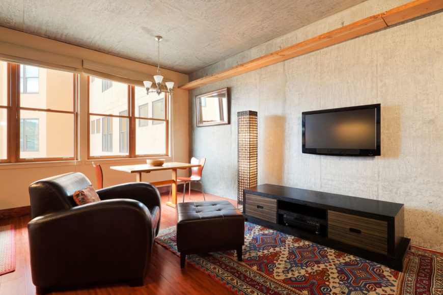 this small living room is furnished with a single leather chair the ottoman in this