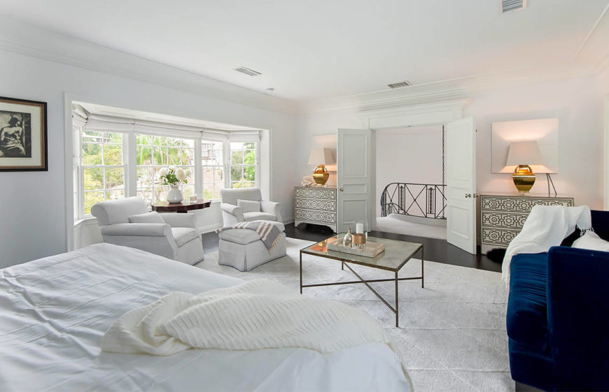 This spacious master bedroom is in white and utilizes lamps and mirrors to help reflect light throughout the spacious room. A seating area is arranged in front of the large bay windows. A splash of color is brought in via the navy velvet sofa.