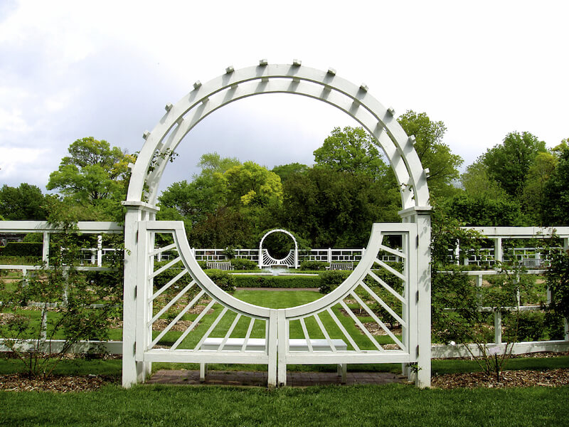 a thick white wooden arbor with a single gate attached to a modern style decorative fence - Arbor Design Ideas