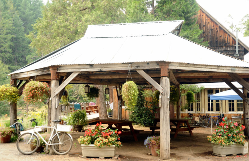 here is a rustic style pavilion with worn and natural wood beams two picnic benches - Patio Pavilion Ideas