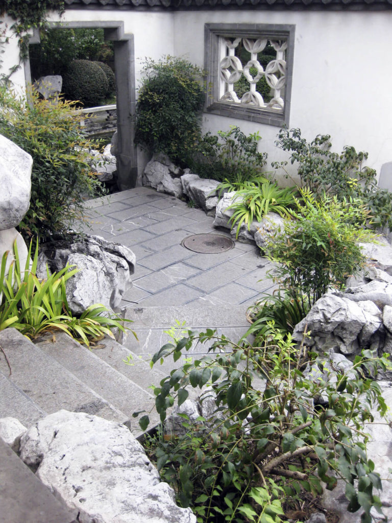 here we see a concrete stairway leading to a small patio and archway the rocks - Rock Garden Patio Ideas