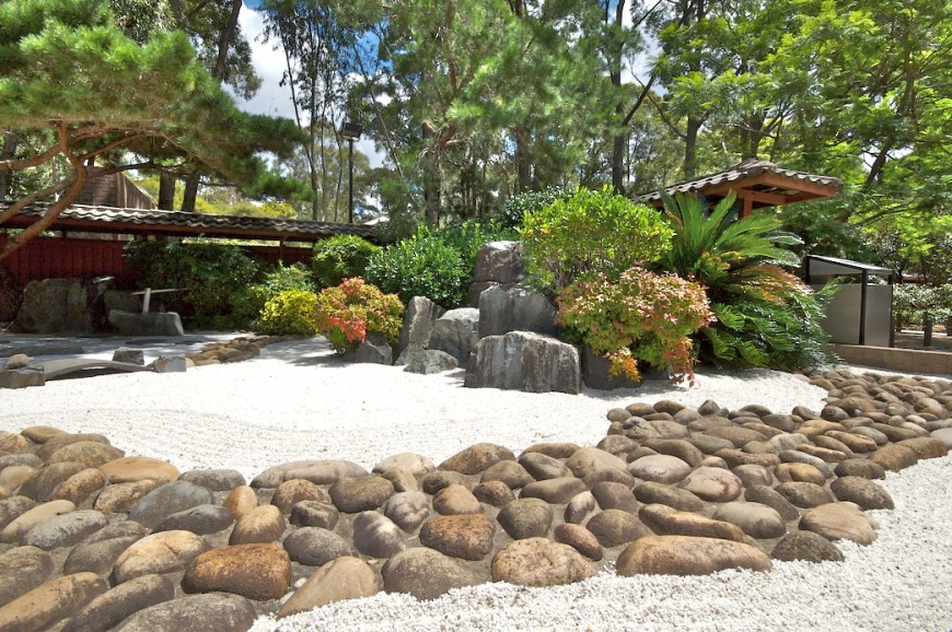 here is a zen garden outlined by a large rock ring it separates the garden