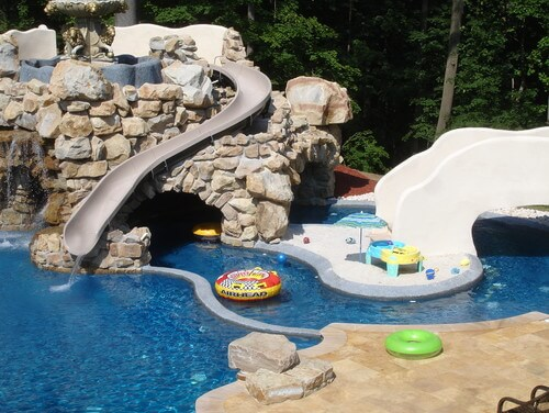 water slide placed along a castle esque stone structure in this water