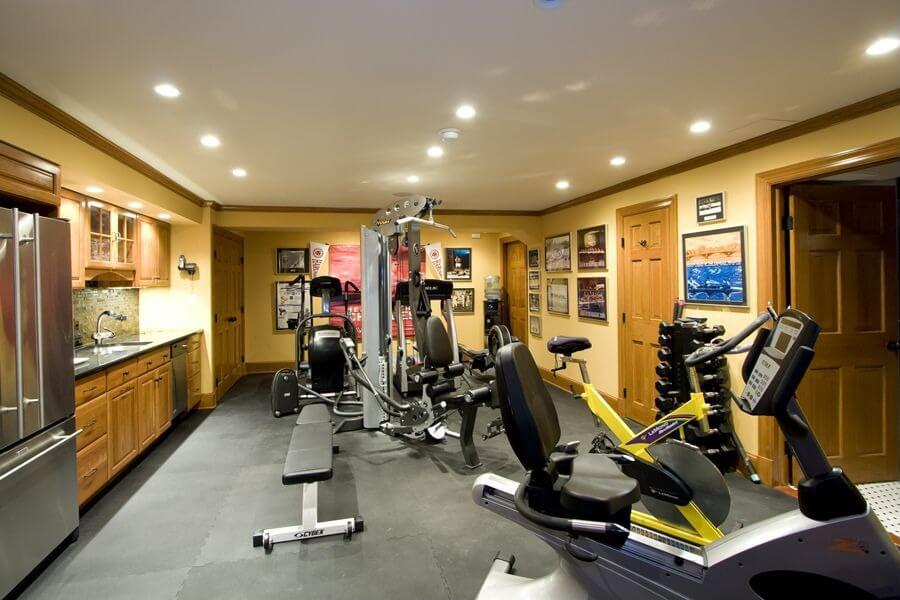enclosed home gym in basement of home with cardio equipment and weight machines small kitchen - Home Gym Design Ideas