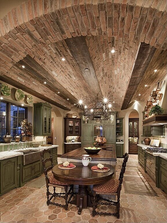 Luxury Kitchen With Arched Brick Ceiling And Long Center Island With An Attached Cozy Table For