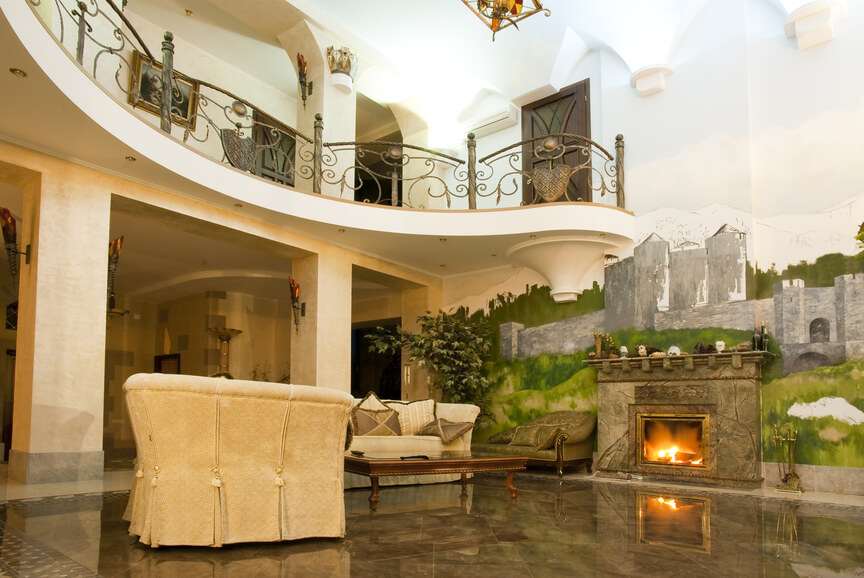 Palatial living room with 2-story ceiling surrounded by upper-level landing. Large mural on wall with fireplace.