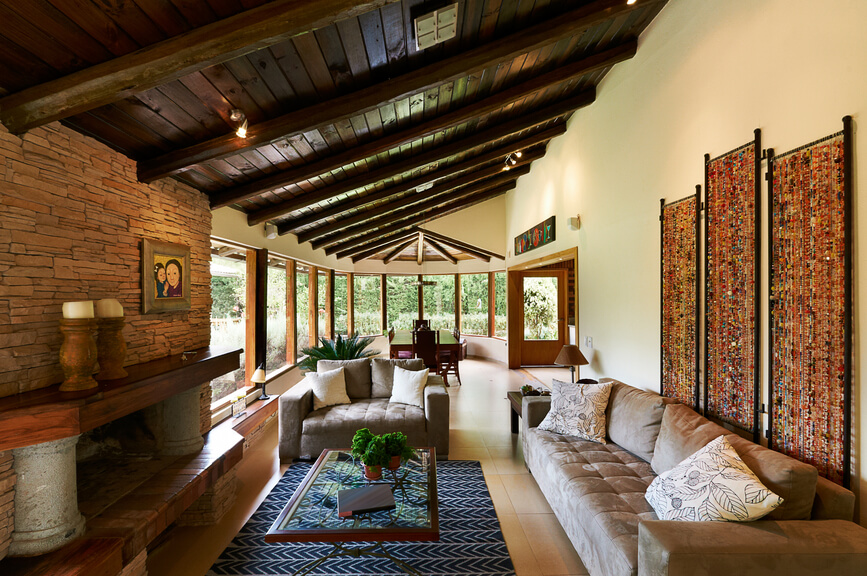 Rustic living room with sloped wood beamed ceiling, brick wall, large wood fireplace mantle on tile floor.