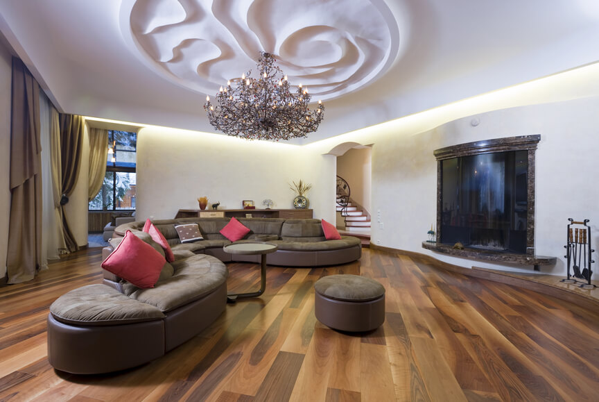 Large living room space with winding sectional sofa, round ottoman, large floating fireplace, wood floors and engraved ceiling design.