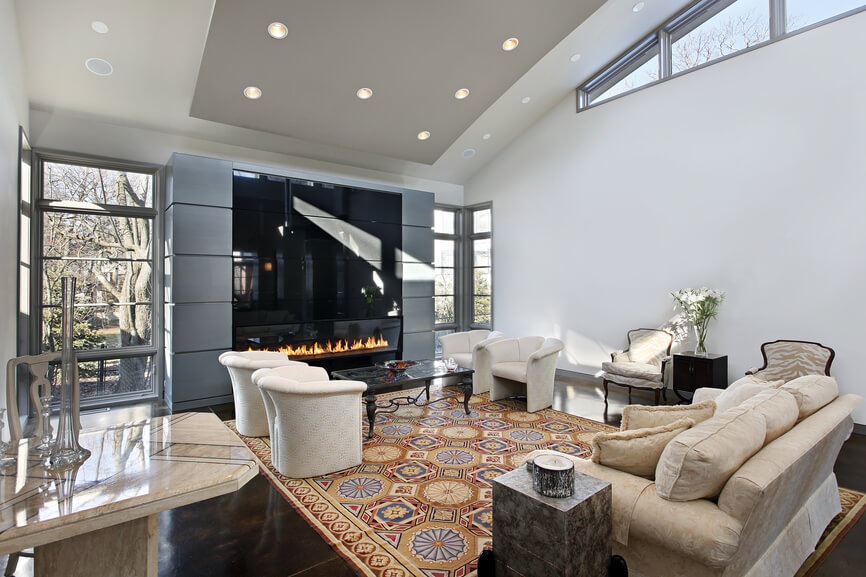 Predominantly white living room design with modern gas fireplace framed with windows. Wood is dark wood topped with a large patterned rug.