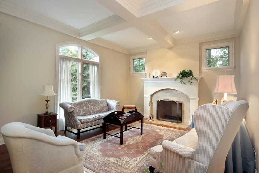Intimate living room with exposed white beams against white ceiling, white walls, white fireplace, wood floor and blue and white furniture.