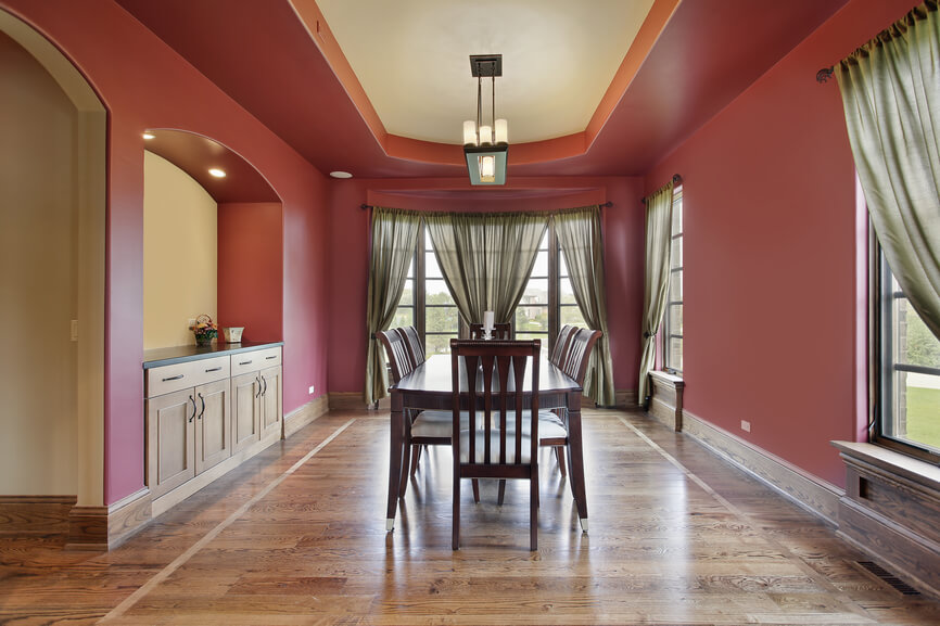Dining Room With Red Walls Tray Ceiling And Wood Flooring Built In Cabinets
