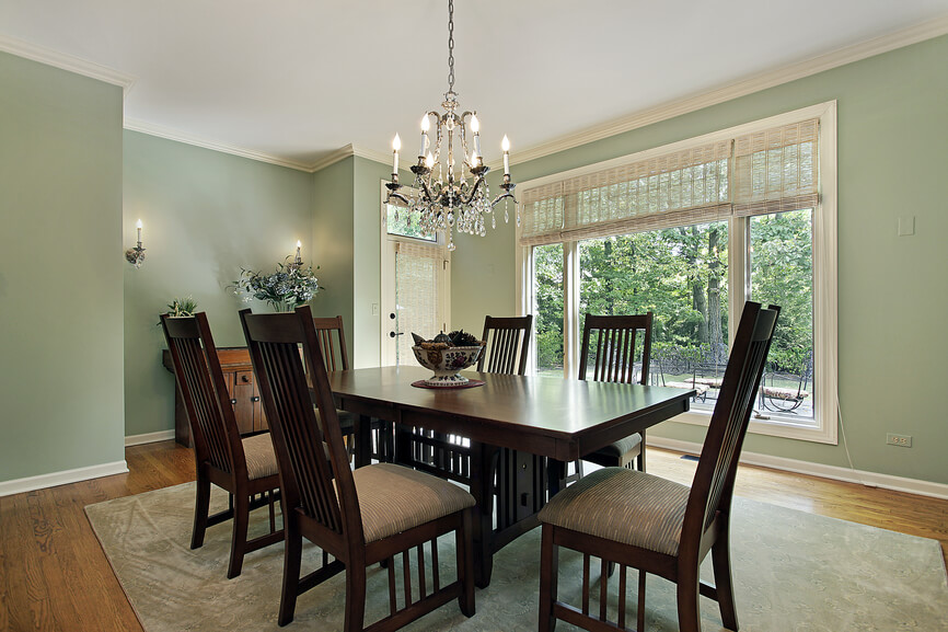 dining room in mint green and white color scheme with light wood floor and dark wood