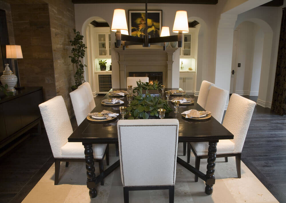 Open concept home with designated dining area in front of fireplace. Dark wood  dining table