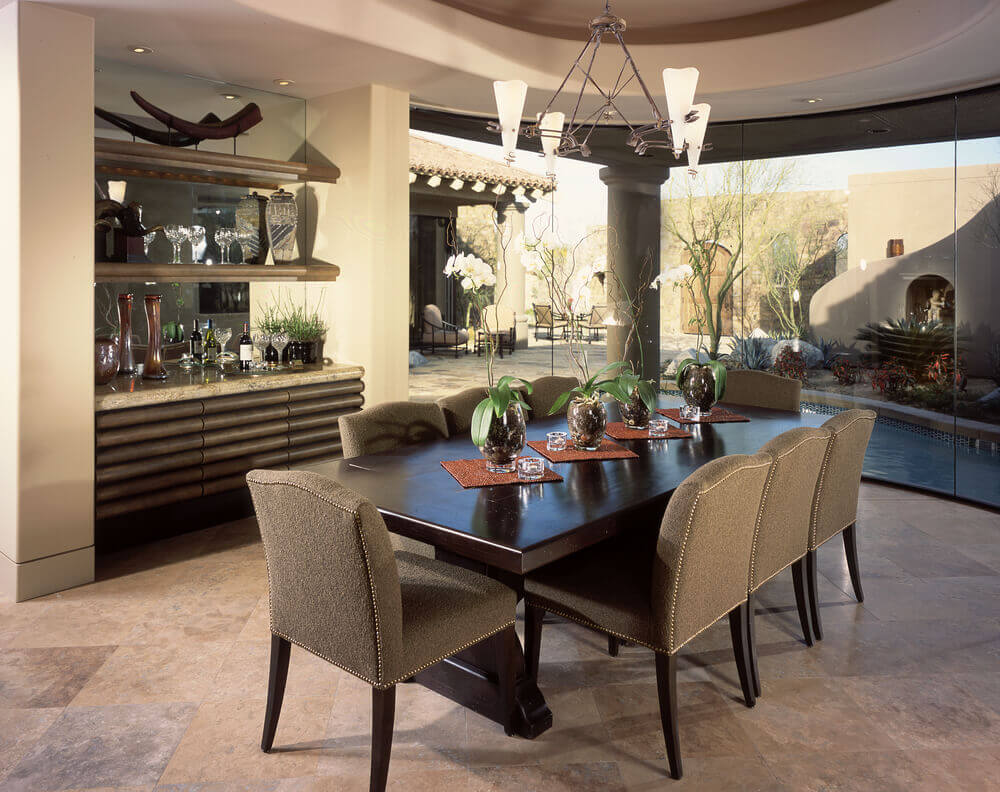 Designated dining room with floor-to-ceiling windows looking out into the home's courtyard and pool