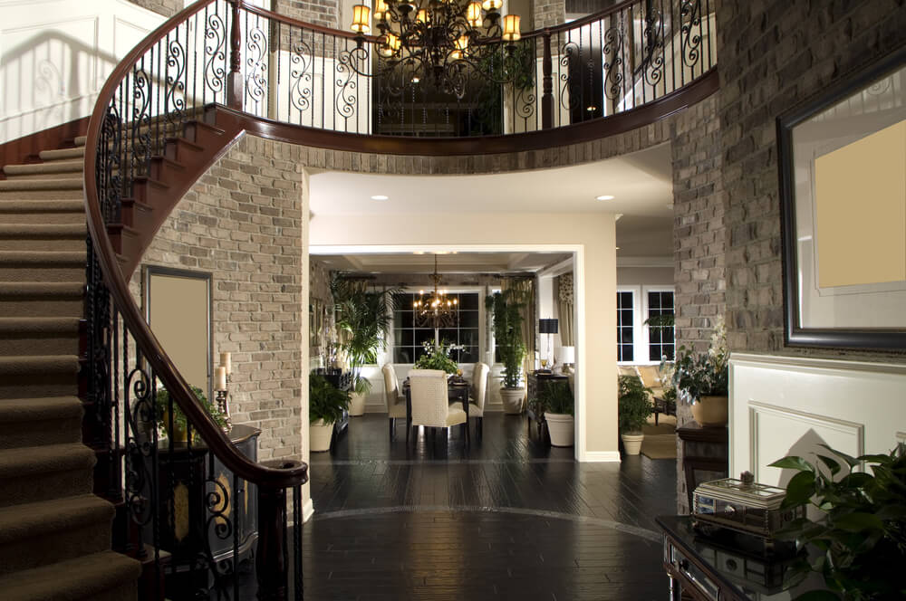 Circular foyer with view of upper landing and arched stairs descending into the center of the foyer.  Foyer walls in grey brick with dark wood floor.