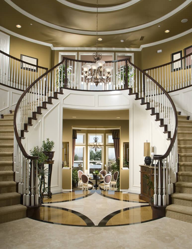 Grand circular foyer with arched carpeted stairs wrapping around both sides of the entrance.  Foyer is two stories in height and leads directly into a small dining room.