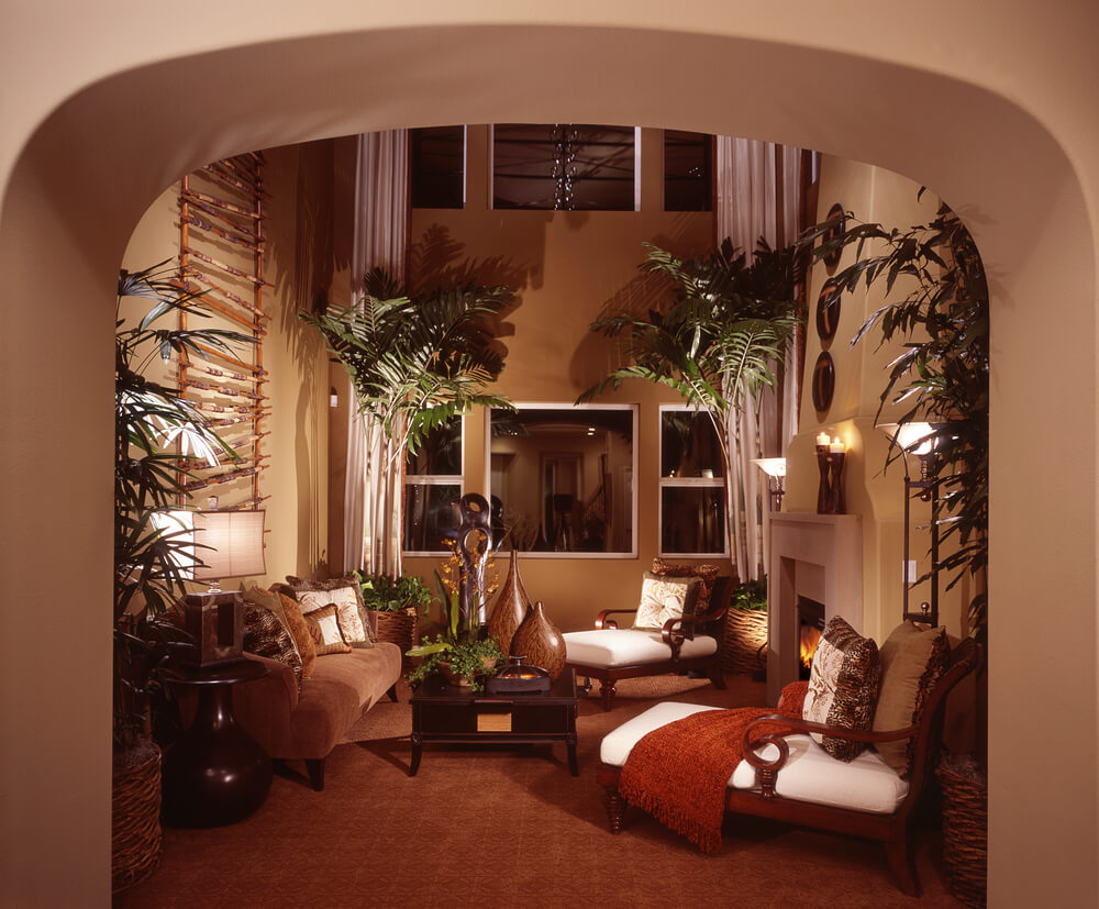 Tropical themed living room design with tall ceiling, trees, plants and formal tropical furniture accessed through an arched doorway.