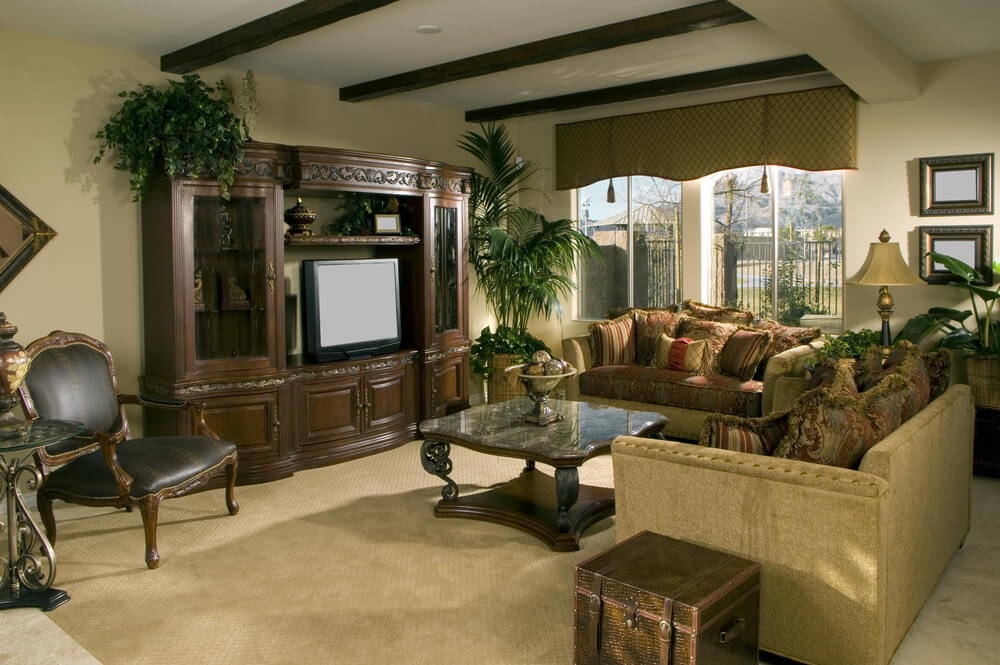 Wood beams against a white ceiling cap this large living room which includes a large ornate wood entertainment unit facing rustic furniture on beige carpeting