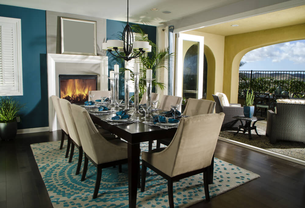 wood floor blue and white rug centered under the dining table that