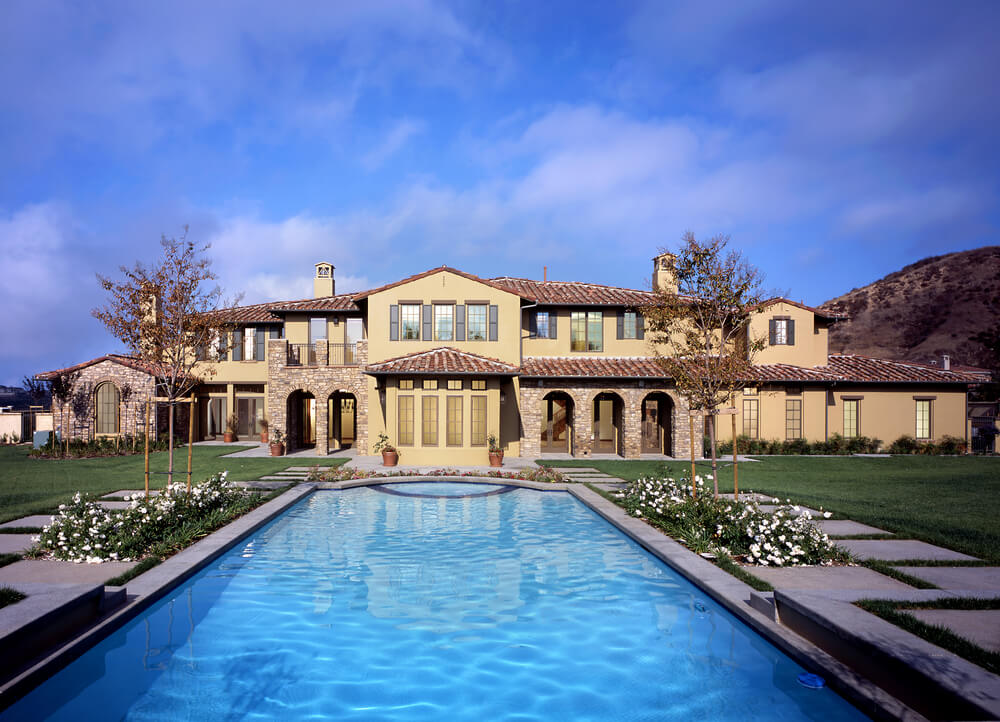 large pool with patio surrounded by sprawling lawn