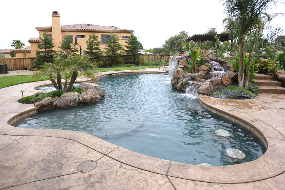 huge pool complex with patio rocks and waterfall