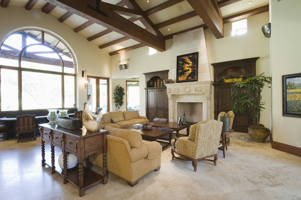 Picture of a large open living rooms space with tall fireplace, elevated ceiling looking out a 2-story arched window.