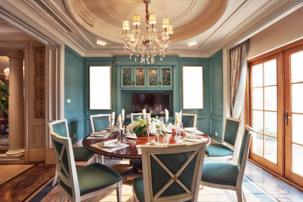 ornate dining room table and chairs. ornate dining room in bright blue. table is round with eight blue chairs and