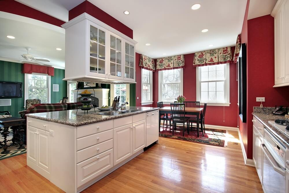 White kitchen with red walls. Island is white with drop-down cabinet  overhead.